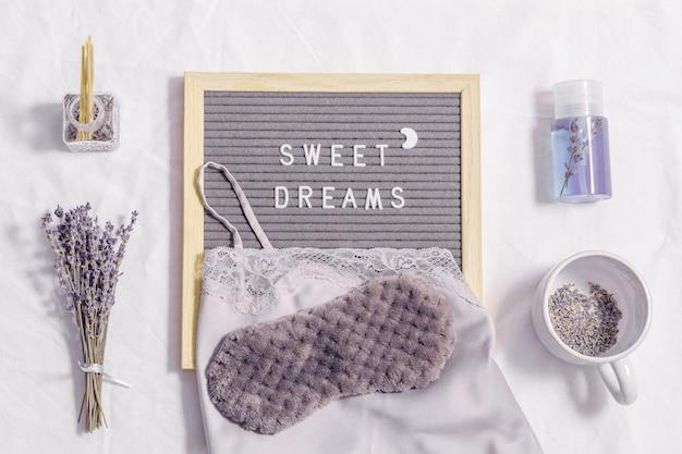Concepto de sueño de noche saludable taza de té de lavanda pijamas de seda aromas de antifaz para dormir