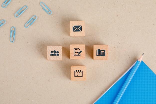 Concepto de suministros de oficina con iconos en cubos de madera, papelería conjunto endecha plana.