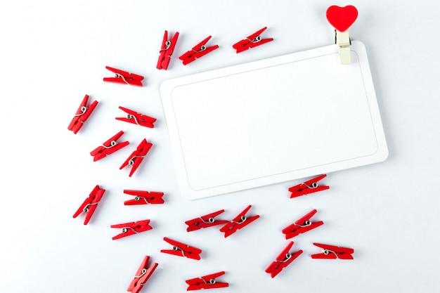 Concepto de tarjeta de amor pinza para la ropa con el corazón en un blanco