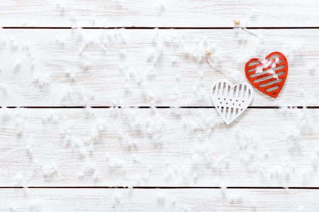Concepto de tarjeta del día de san valentín, copos de nieve dos corazones rojos blancos en la mesa de madera clara cubierta de nieve, tarjeta de fondo de vacaciones románticas, amor y relaciones, venta de vacaciones, vista superior, espacio de copia