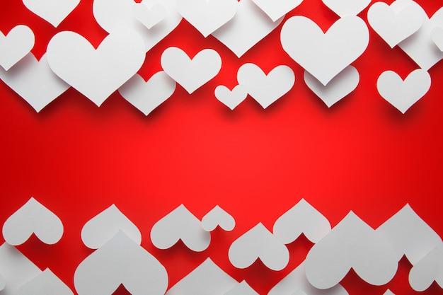El concepto de la tarjeta del día de san valentín con los corazones rojos forma en fondo rojo