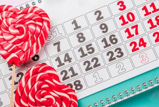 Concepto de tarjeta de felicitación de fondo rosa claro del día de san valentín dos piruletas de corazón rojo o dulces dulces en palos y calendario