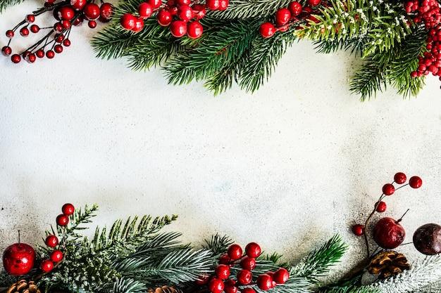 Concepto de tarjeta de navidad: marco hecho con ramas de árboles de hoja perenne con decoración de nieve y adornos sobre fondo de piedra con espacio de copia