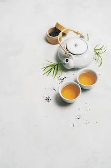Concepto de té asiático, dos tazas de té blanco, tetera, juego de té, palillos, estera de bambú