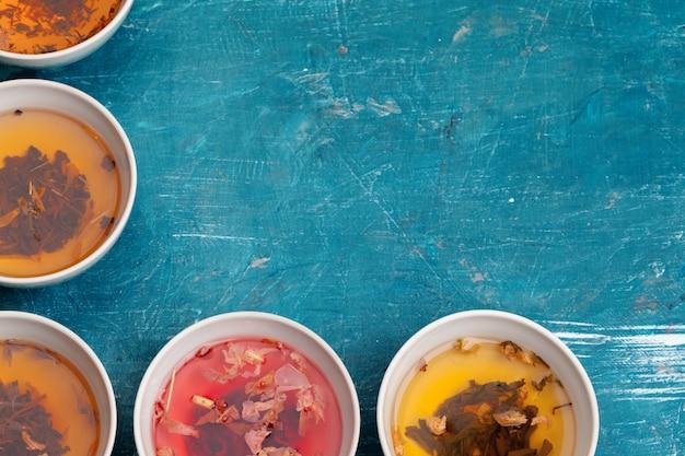 Concepto de té diferentes tipos de té seco en cuencos de cerámica y tazas de té aromático.