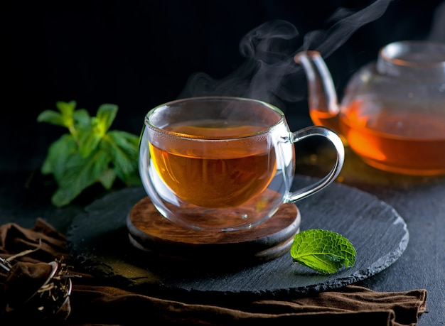 Concepto de té, tetera con té rodeado sobre fondo de madera, ceremonia del té, té verde en una taza transparente