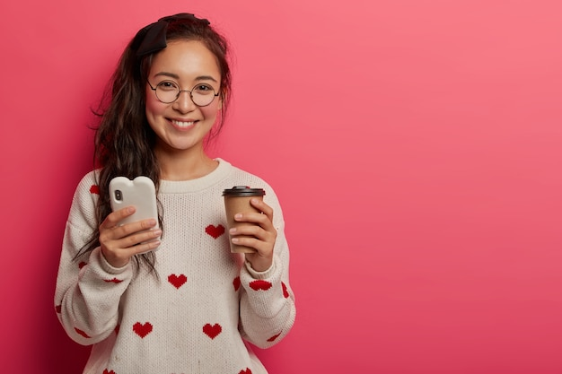 Concepto de tecnología, comunicación y estilo de vida. bastante joven con gafas redondas usa un teléfono inteligente para leer blogs y mensajes geniales, bebidas, café para llevar, aplicaciones de descargas, se encuentra en el interior.