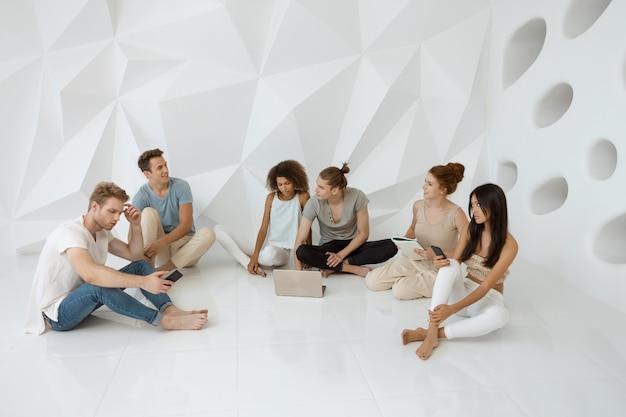 Concepto de tecnología de conexión de dispositivos digitales de personas diversas. grupos de diferentes personas sentadas.