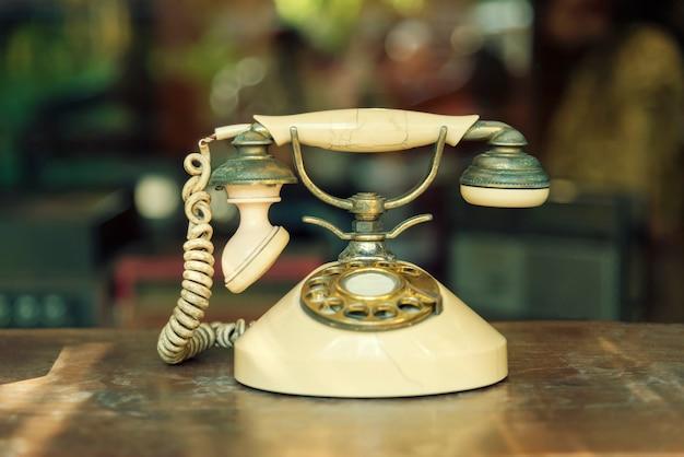 Concepto de tecnología de conexión. teléfono viejo en la tabla de madera con el fondo borroso.