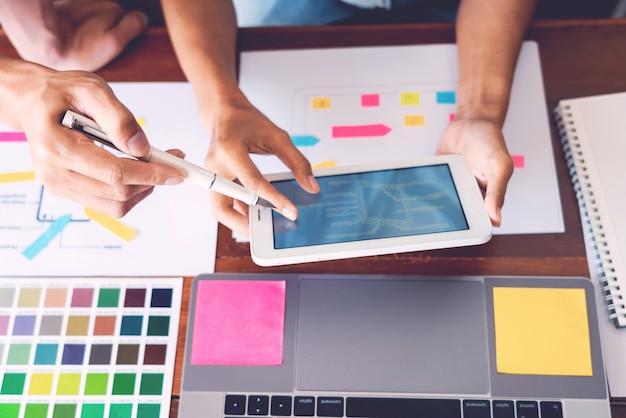 Concepto de tecnología empresarial, diseñador de equipo creativo que elige muestras con ui / ux que se desarrolla en el diseño de diseño de bocetos en la aplicación de teléfono inteligente para la tabla de diseño de interfaz de usuario móvil.