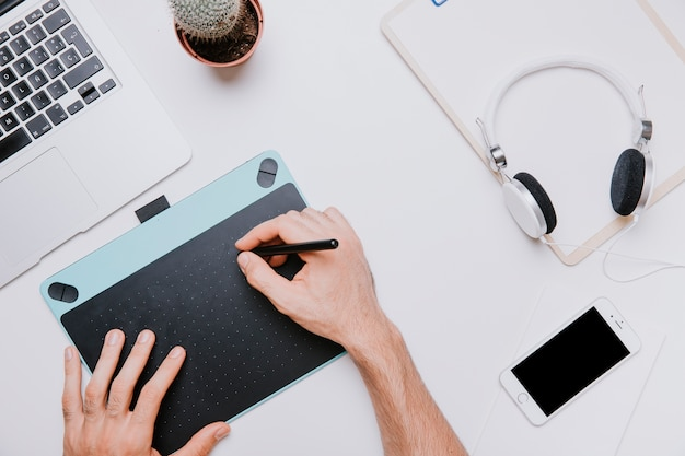 Concepto de tecnología y escritorio con manos dibujando
