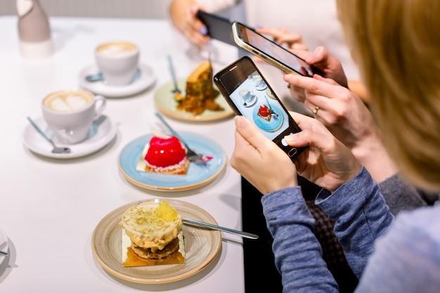 Concepto de tecnología, estilo de vida, amistad y personas: tres mujeres jóvenes felices con teléfonos inteligentes haciendo fotos de sus tazas de café y postres en un café en el interior