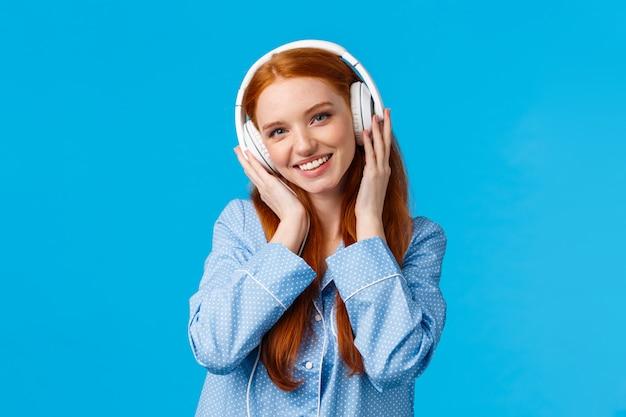 Concepto de tecnología, estilo de vida y personas. linda pelirroja en pijama, escucha música en los auriculares, disfruta de buenos ritmos en los auriculares, buena calidad, nuevas canciones, pared azul de pie