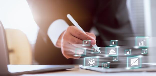 Concepto de tecnología internet y redes, mano de hombre de negocios con pluma blanca con icono de medios en pantalla digital.