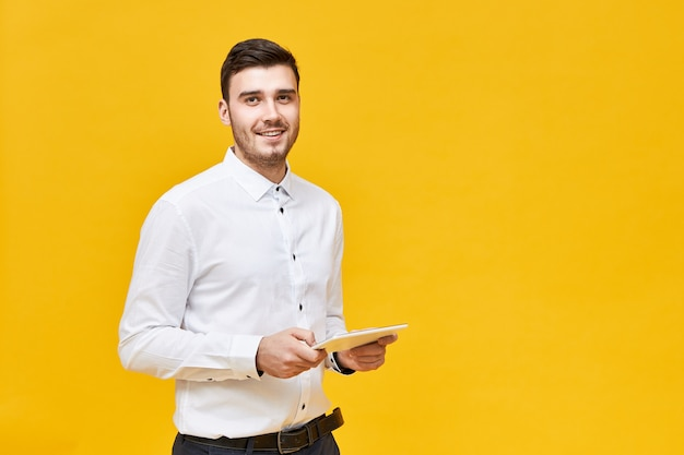 Concepto de tecnología moderna y dispositivos electrónicos. gerente masculino joven positivo elegante con tableta digital para el trabajo. hombre de negocios, en, ropa formal, tenencia, panel táctil, computadora portátil