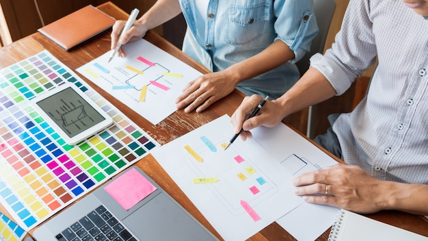 Concepto de tecnología de negocios, diseñador de equipo creativo que elige muestras con ui / ux que se desarrolla en el diseño de diseño de boceto en la aplicación de teléfono inteligente para la tabla de diseño de interfaz de usuario móvil.