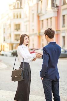 Concepto de tecnología y personas de asociación empresarial empresario sonriente y apretón de manos de mujeres empresarias