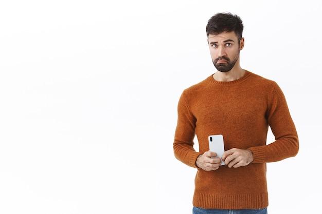 Concepto de tecnología, personas y comunicación. retrato de hombre barbudo joven y guapo tratando de actuar con normalidad, sosteniendo el teléfono móvil cerca del pecho como grabando videos en secreto o tomando fotos espiando