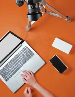 Concepto de tehnobloger. manos de mujeres desempaquetando nuevo teléfono inteligente con caja y blogs con cámara en trípode, portátil sobre fondo naranja. vista superior
