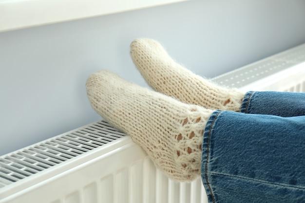 Concepto de temporada de calefacción con piernas en botas tejidas en radiador.