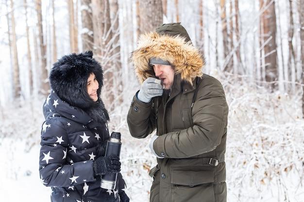 Concepto de temporada y caminata - pareja feliz bebiendo té caliente en el bosque de invierno
