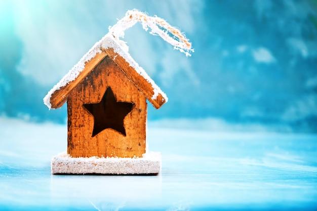 Concepto de temporada y vacaciones. juguete decorativo de la casa en un fondo azul del invierno del hielo. enfoque selectivo