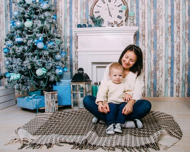 Concepto de temporadas de navidad, año nuevo, invierno y vacaciones. familia. madre y niño cerca de árbol de navidad.