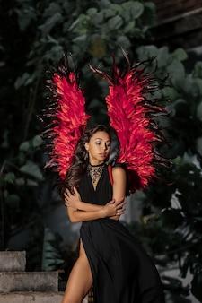 Concepto de tentadora. mujer en cara apasionada juego de rol. chica sexy demonio en vestido negro con alas rojas, demonio lleno de deseo parado en las escaleras