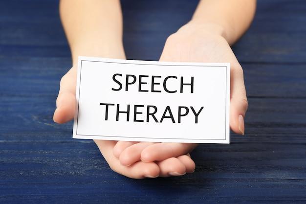 Concepto de terapia del habla. manos sosteniendo la tarjeta en la superficie de madera azul