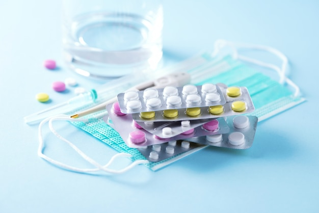 Concepto de terapia, prevención de la gripe viral, ataque viral, resfriados, antibióticos y vitaminas, máscaras médicas protectoras sobre fondo azul. coronavirus (covid-19. copia espacio