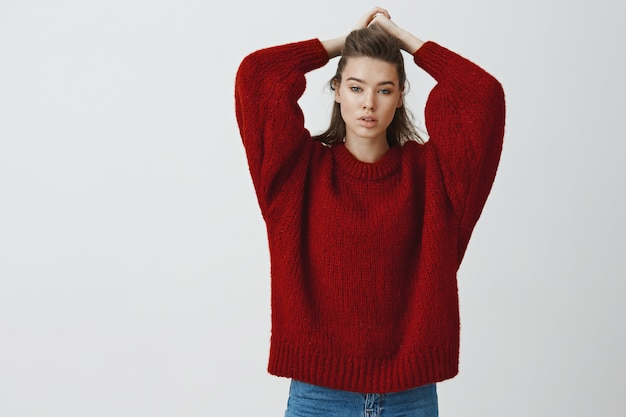 Concepto de ternura, sensualidad y belleza. encantadora joven y delgada mujer europea de 25 años en suéter rojo suelto que se peina el cabello tocando el corte de pelo mientras mira detenidamente