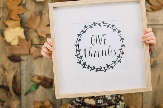 Concepto de thanksgiving con niña sujetando marco