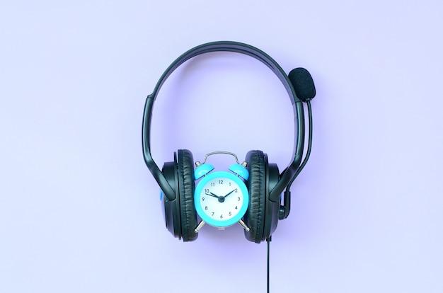 Concepto de tiempo para escuchar música. reloj despertador y auriculares