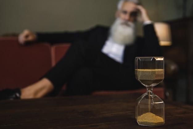 Concepto de tiempo - hombre mayor mirando el reloj de arena