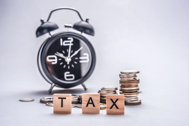 Concepto de tiempo de impuestos con bloques de madera y monedas sobre fondo blanco