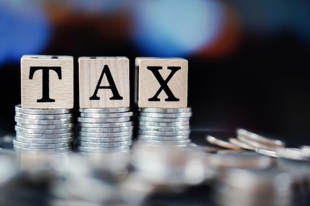 Concepto de tiempo de impuestos con palabra de impuestos y pila de monedas