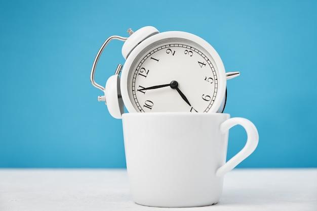 Concepto de tiempo de mañana. despertador retro blanco en taza sobre fondo azul.