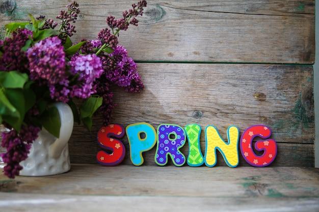 Concepto de tiempo de primavera con flores lilas en bouquet y palabra de primavera con letras coloridas brillantes