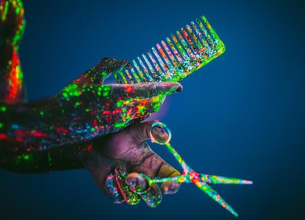 Concepto. las tijeras y el peine están pintados con polvo ultravioleta. estilo y moda. mano masculina del peluquero estilista tiene tijeras y peine de madera.