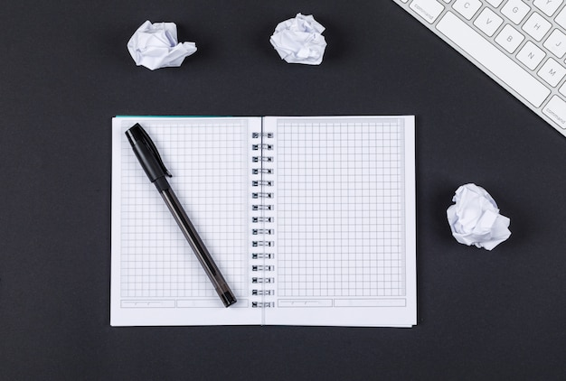 Concepto de tomar nota con el cuaderno, lápiz, papel picado, teclado en la vista superior de fondo negro. imagen horizontal