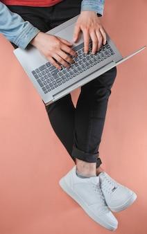 Concepto de trabajador en línea. hombre inconformista escribiendo en la computadora portátil y se sienta en rosa