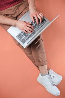 Concepto de trabajador en línea. hombre en zapatillas blancas y pantalones beige escribiendo en la computadora portátil y se sienta en rosa