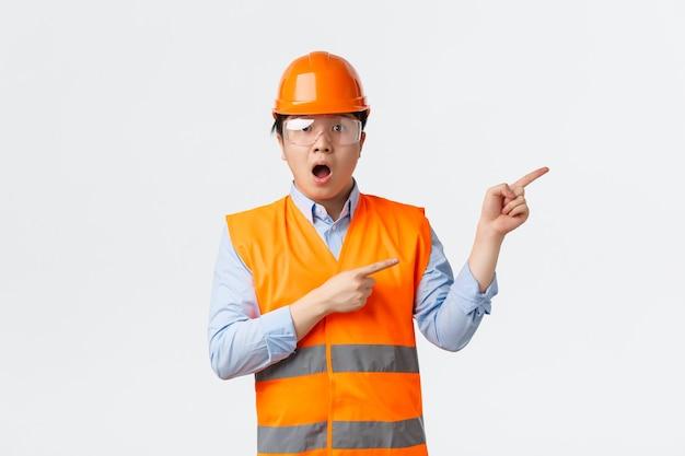 Concepto de trabajadores industriales y del sector de la construcción. asombrado e impresionado arquitecto de sexo masculino asiático, ingeniero con casco protector y gafas de seguridad trabajando en la fábrica, apuntando hacia la esquina superior derecha asombrado