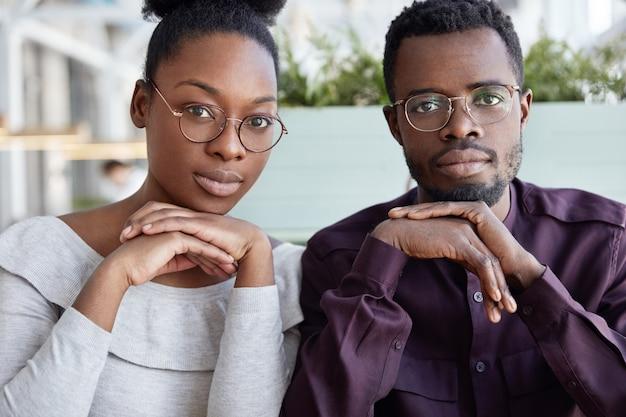 Concepto de trabajo en equipo y cooperación. los colegas masculinos y femeninos afroamericanos exitosos se sientan cerca uno del otro, usan anteojos