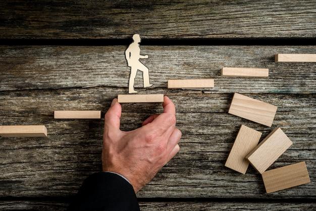 Concepto de trabajo en equipo con el empresario sosteniendo escaleras