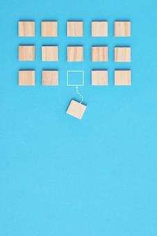 Concepto de trabajo en equipo y liderazgo. grupo de bloques de madera y uno a otro bloque en otra dirección sobre fondo azul.