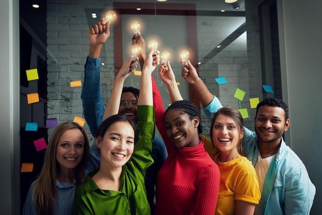 Concepto de trabajo en equipo y lluvia de ideas con empresarios que comparten una idea con una lámpara