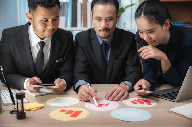 Concepto de trabajo en equipo de negocios. lluvia de ideas sobre estrategias de marketing. papeleo y digital en espacio abierto.