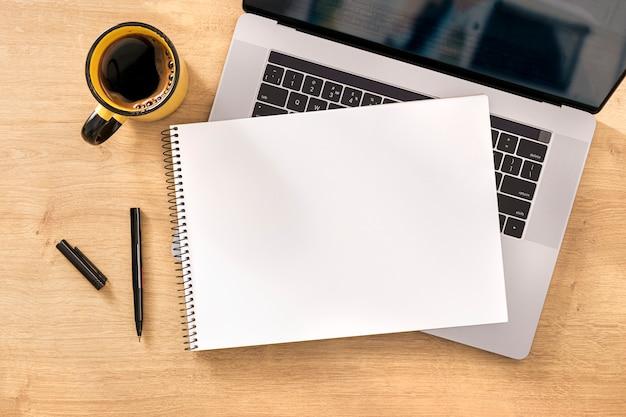 Concepto de trabajo en línea cuaderno en blanco con laptop y taza de café en la vista superior de la mesa de madera