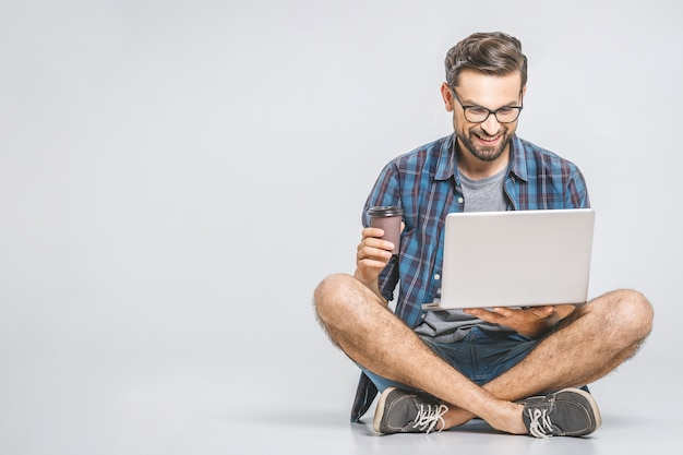 Concepto de trabajo en línea. hombre de negocios informal relajado trabajando y navegando por internet en la computadora portátil con café. independiente sentado y escribiendo en el teclado del ordenador portátil en la oficina en casa.